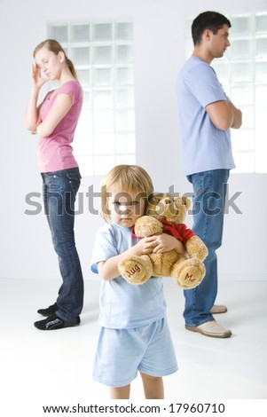 Young parents standing back to back. Theirs daughter huging teddy bear and looking at camera.