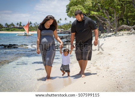 Young parents teaching their toddler to walk. They are expecting another child soon.