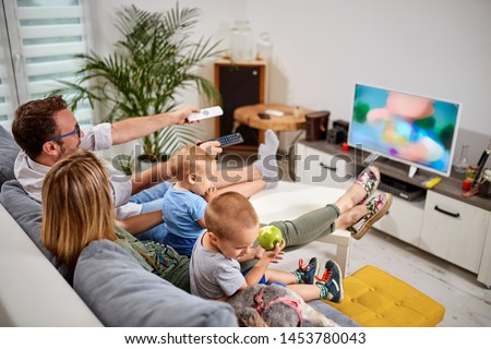 Young parents watching TV with baby boys.