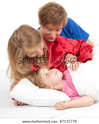 young parents with beautiful daughter in bed, white background