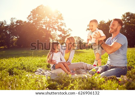 Young parents with children on picnic in nature at summer