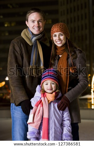 Young parents with daughter standing outdoors in winter