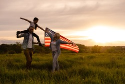 Young parents with their daughter holding American flag in countryside at sunset. Independence Day celebration