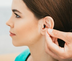 Young patient with Intra-ear hearing aid, close-up on female ear. The hearing solution, audiologist inserting hearing aid