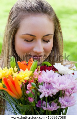 Young peaceful girl closing her eyes while smelling a beautiful bunch of flowers