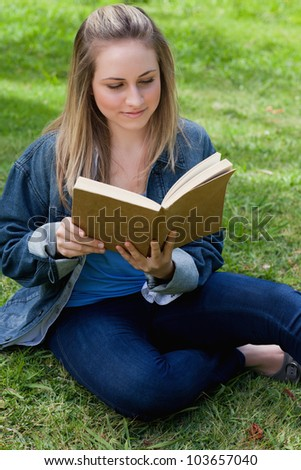 Young peaceful girl reading a book while sitting on the grass in a public garden