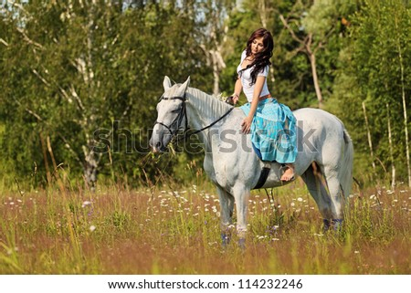Young peasant woman rides a horse