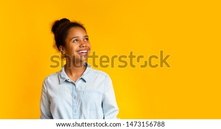 Young pensive african girl looking upwards at empty space on yellow studio background, panorama