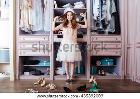 Young pensive beautiful girl choosing shoes in her wardrobe