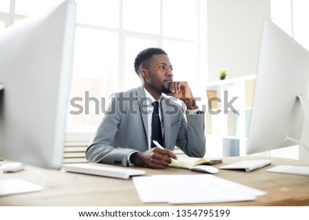 Young pensive businessman looking at data on computer screen while making notes in notebook by workplace