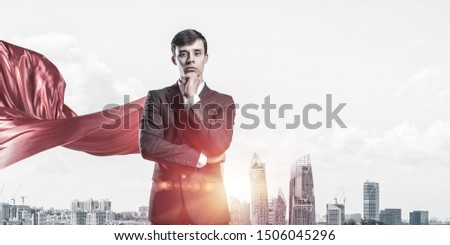 Young pensive businessman wearing red cape against modern city background