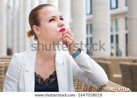 Young pensive contemplative woman in suit, jacket sitting daydreaming or waiting for someone in terrace of cafe outdoor. Thoughtful lady dreaming, thinking about future