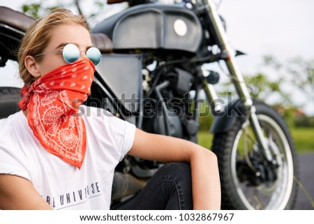 Young pensive female driver wears bandana and stylish sunglasses sits near speed motorbike, has outdoor journey alone, enjoys good rest and wonderful nature view. Transport and lifestyle concept