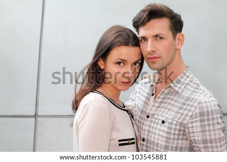 Young pensive man and woman stand near gray wall and look at camera