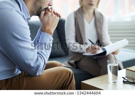 Young pensive man sitting on couch with his hands by mouth while listening to female psychologist