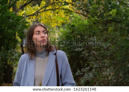 Young pensive woman alone in autumn city street
