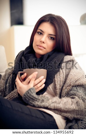 Young pensive woman in cozy warm clothings with cup of coffee