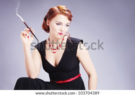 Young pensive woman in style of sixties  dreaming of something and smoking