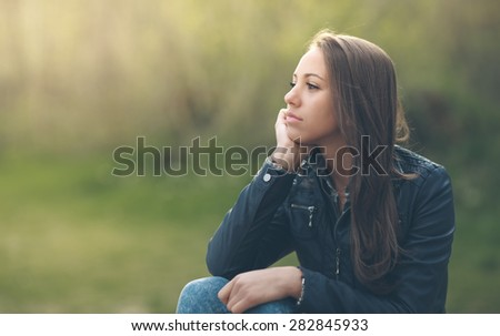 Young pensive woman relaxing at the park and sitting on grass, vegetation on background