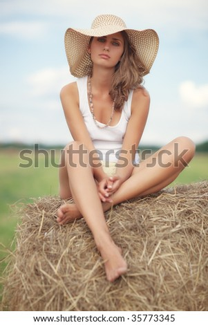 Young pensive woman sitting on a haystack.