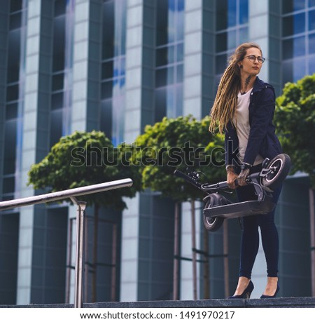Young pensive woman with dreadlocks and glasses is posing for photographer with folded scooter.