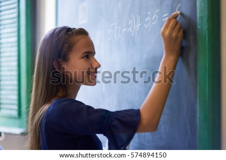 Young people and education. Group of hispanic students in class at school during lesson. Portrait of happy girl doing math exercise at blackboard
