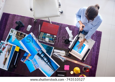 Young people and small business. Busy woman at work as photographer in lab. Beautiful girl cropping, cutting color prints for photo exhibition. Artist and art profession.