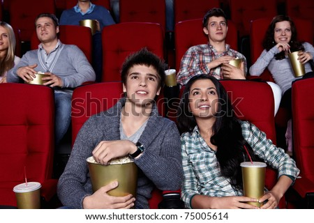 Young people are closely watching a movie at the cinema - stock photo