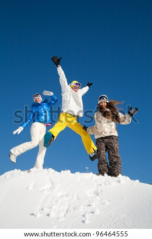 Young people are enjoying the sun and snow, bouncing in the air