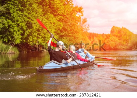 Young people are kayaking on a river in beautiful nature. Summer sunny day in outdoor