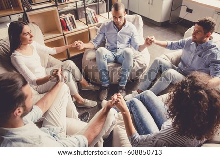 Young people are sitting in circle, holding hands and meditating #608850713