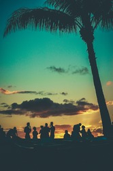 Young People At Retro Styled Hawaiian Sunset Beach Party
