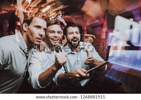 Young People. Dance Club. Sing. Microphone.Nightclub. Party Maker. Birthday. Karaoke Club. Celebration. Handsome Men. Beautiful Girls. Dancing People. Men Sing. Boys. Great Mood. Against the Backdrop.