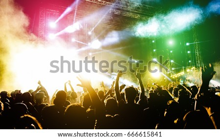 Shutterstock Young people dancing and having fun in summer festival party outdoor - Crowd with hands up celebrating fest concert event - Soft focus on center bottom hand with background flare - Contrast filter