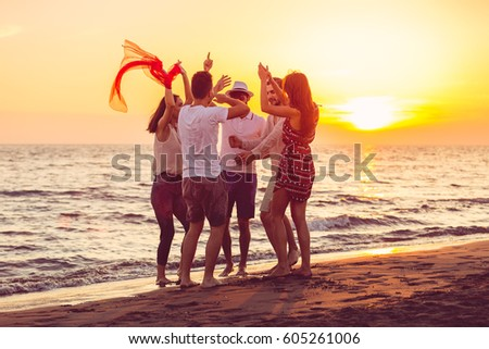 Young People Dancing On Beach at Sunset #605261006