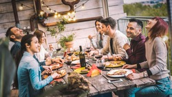 Young people dining and having fun drinking red wine together on balcony rooftop dinner party - Happy friends eating bbq food at restaurant patio - Millennial life style concept on warm evening filter