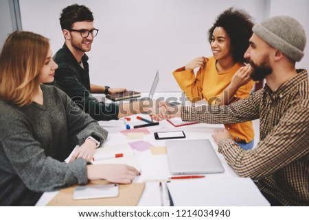 Young people dressed in casual wear handshaking and collaborating with each other during brainstorming meeting at table in office.Cooperation of multicultural students for successful results