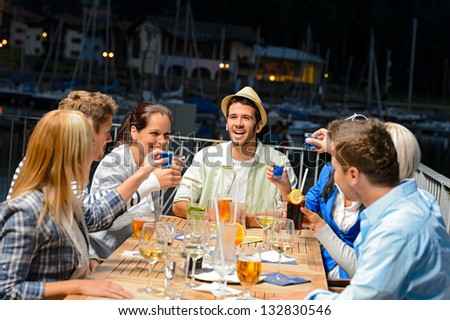 Young People Drinking Shots At Outside Bar Night Out