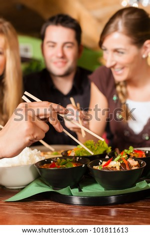 Young people eating in a Thai restaurant; they eating with chopsticks - stock photo