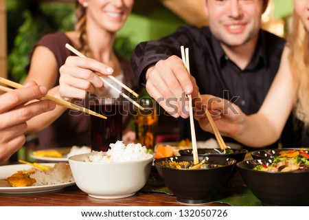 Young people eating in a Thai restaurant they eating with chopsticks