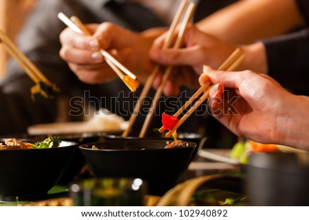 Young people eating in a Thai restaurant, they eating with chopsticks, close-up on hands and food ストックフォト ©