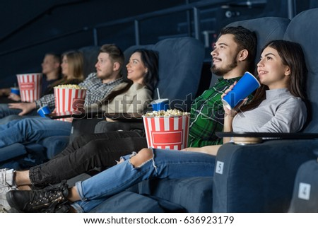 Young people enjoying a movie at the cinema. Beautiful couple relaxing on comfortable seats watching a film at the movie theatre having a date couples people entertainment holidays leisure dating