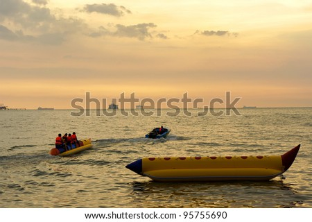 Young people enjoying a ride on a banana boat at tropical beach during sunset.
