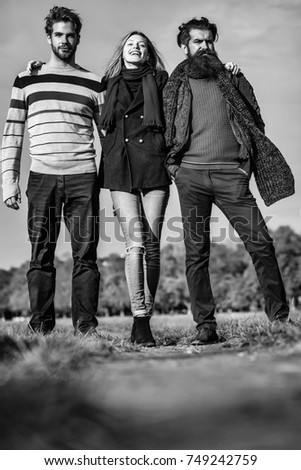 Young people friends of pretty girl and two bearded men outdoors in park on autumn day on natural background