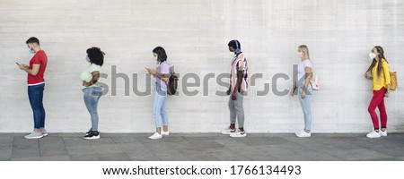 Young people from different cultures and race waiting in queue outside shop market while keeping social distance - Corona virus spread prevention concept