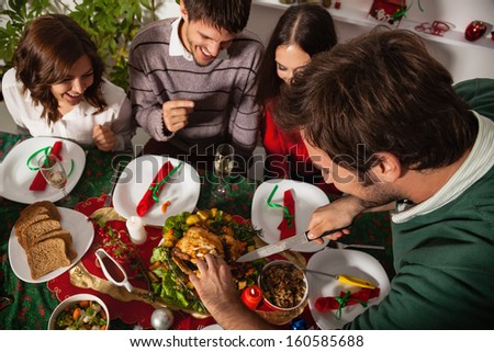 Young people gather together for Christmas dinner.