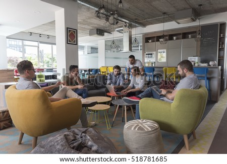 young people group in modern office have team meeting and brainstorming while working on laptop and drinking coffee