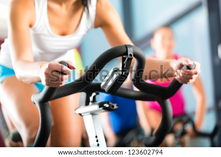 Young People - group of women and men - doing sport biking in the gym for fitness - stock photo