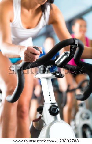 Young People - group of women and men - doing sport Spinning in the gym for fitness - stock photo