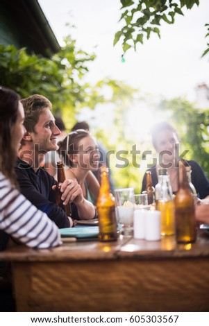 Young people having fun around a table on the terrace while their friends roast the meat on the bbq at the background. Shot with flare